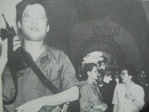 """Ang anak ng Pangulo na si Noynoy Aquino habang pinoprotektahan ang kanyang ina noong kudeta ng Disyembre 1989.  Mula sa aklat ng PCIJ na """"Kudeta: A Challenge to Philippine Democracy."""""""