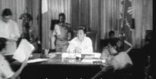 Si Edgar Jopson habang iwinawasiwas sa harapan ng pangulo ang kasunduan.  Mula sa Batas Militar.
