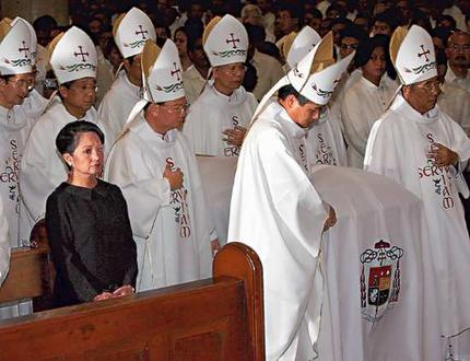 Ang mga obispo ng Simbahang Katoliko buhat-buhat ang mga labi ni Jaime Cardinal Sin, 2005.  Ang mahal na Pangulong Gloria Macapagal Arroyo ang naka-itim.