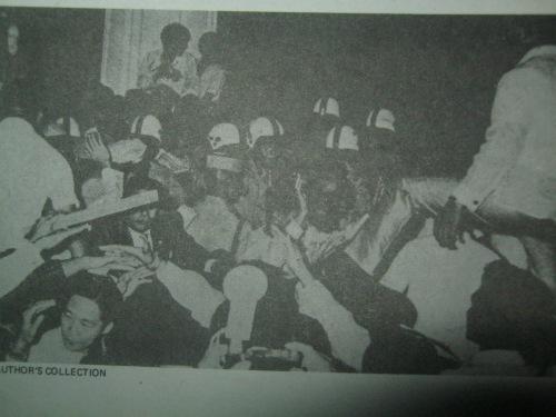 Si Pangulong Marcos habang pinapaulanan ng debris ng mga raliyista, January 26, 1970.  Mula sa Ninoy Aquino:  The Willing Martyr.