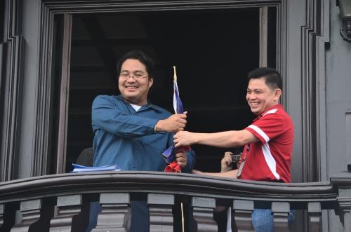 Si Xiao Chua habang ipinapasa ang Watawat ng Pilipinas kay Sir Angelo Aguinaldo sa mismong balkonahe ng bintana kung saan ipinroklama ng lolo niya sa tuhod ang independensya.