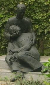 Monumento ng paggunita sa masaker sa De La Salle College na nagpapakita ng isang pari na nagbibigay absolusyon sa isang namamatay na Borther.