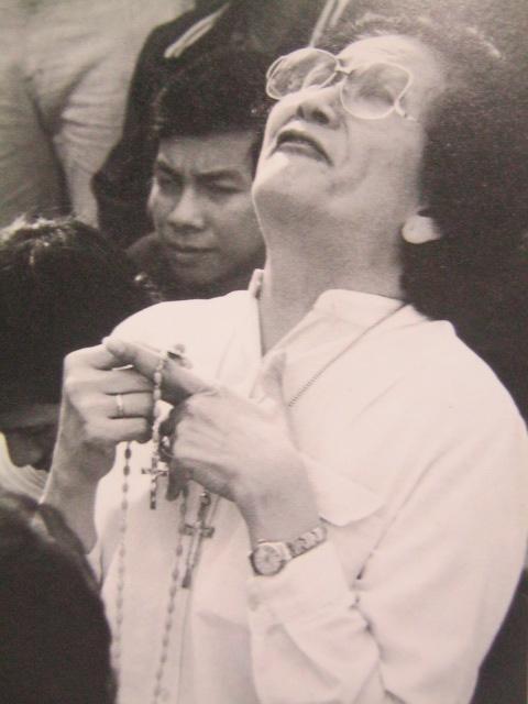 Isang babaeng nagrorosaryo habang nakaluhod sa isang tangke noong Himagsikang EDSA.  mula sa James Reuter Foundation.