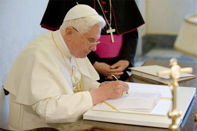 Si Pope Benedict XVI habang pinipirmahan ang mga kopya ng kanyang unang ensiklikal Deus Caritas Est