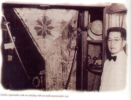 Si Heneral Aguinaldo sa harap ng pinaniniwalaang unang watawat ng Pilipinas.  Mula sa Tahanan ng Kasarinlan.
