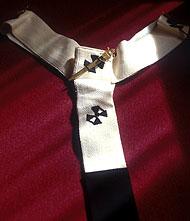 Pallium na may disenyo ng limang krus at tatlong pins.  Sinusuot ng mga arsobispo, mga kardinal at santo papa.
