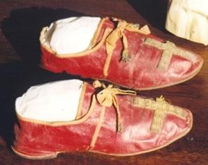 Lumang pulang sapatos ng isang Santo Papa na may krus na disenyo.