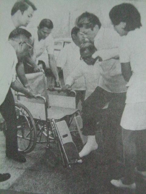Si Gerry habang tinutulungang maupo sa kanyang wheelchair para mangampanya.  Mula kay Senador Jovito Salonga.
