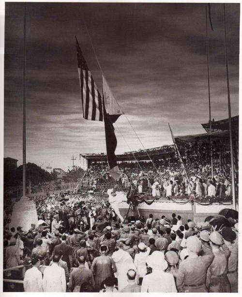 Ang pagbaba ng bandila ng Amerika at ang pagtataas ng watawat ng Pilipinas sa flagpole sa harapan ng Monumento ni Rizal (natatakpan ng entablado) noong July 4, 1946.  Mula sa gov.ph.