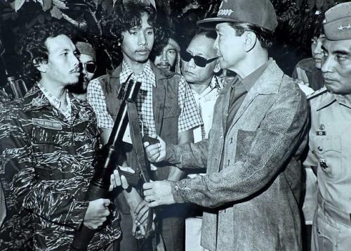 Si Admiral Romulo Espaldon habang nakamasid sa likuran ni Pangulong Ferdinand Marcos habang nagpapasuko ng mga rebeldeng Muslim.  Mula sa Kristiyanismo, niyakap ni Espaldon ang Islam.