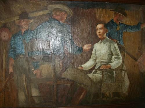 Obra maestra na nagpapakita kay Mabini sa ilalim ng kustodiya ng mga Amerikano.  Makasabit sa Dambanang Pangkasaysayang Mabini sa Tanauan, Batangas