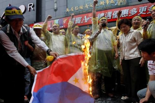 Pagsusunog ng bandilang Pilipino ng mga nagpoprotestang Taiwanese.  Mula sa asianjournal.com.