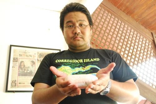 """Si Xiao Chua habang hawak ang natural na namumulang """"blood stone"""" sa Hotel Corregidor.  Kuha ni John Ray Ramos."""
