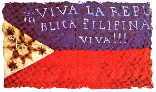 """Isang lumang watawat ng Pilipinas na may nakasulat na """"Viva La Republica Filipina! Viva!!!"""" (Bawal na itong gawin ngayon ayon sa Flag and Heraldic Code).  Dark blue ito.  Mula sa Pambansang Komisyong Pangkasaysayan ng Pilipinas."""