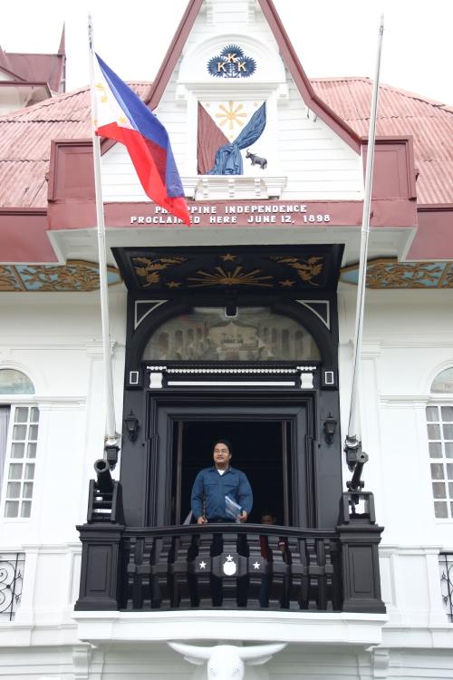 Si Xiao Chua sa Independence Balcony sa ibabaw ng isang kalabaw sa Dambanang Pangkasaysayang Emilio Aguinaldo sa Kawit, Cavite.  Dinagdag lang ang balkonahe sa mansyon noong Dekada 1920.  Kuha ng mga estudyante ni Xiao Chua.