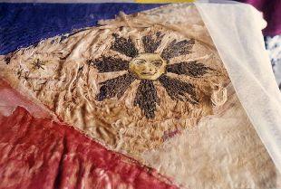 Ang araw sa delikado nang watawat na nasa pangangalaga ng mga Aguinaldo-Suntay sa Emilio Aguinaldo Museum sa Lungsod ng Baguio.  Mula sa watawat.net.