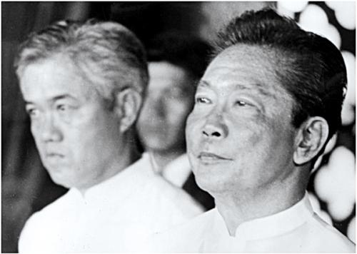 Si Primer Ministro Cesar Emilio Aguinaldo Virata sa likod ni Pangulong Ferdinand E. Marcos.  Mula sa Art Directors Trip Photo Library.