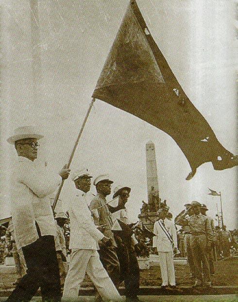 Si Henera Emilio Aguinaldo habang tangan-tangan ang bandilang Aguinaldo-Suntay sa harapan ng monumento ni Dr. Jose Rizal isang Araw ng Kasarinlan (July 4).