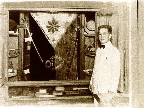 Si Heneral Emilio Aguinaldo sa harapan ng Aguinaldo-Suntay flag na siyang pinaniniwalaan ng ilan na isa sa pinakaunang, kung hindi man ang pinakaunang watawat ng Pilipinas.
