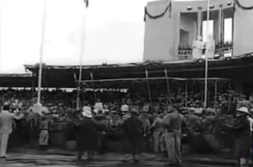 """Ang pansamantalang grandstand na tinakpan ang Rizal Monument sa harapan  ng flagpole sa Luneta.  Mula sa newsreel na """"Philippine Independence."""""""