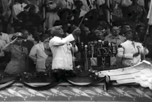 """Si Paul V. McNutt habang ibinababa ang bandila ng Estados, at si Manuel A. Roxas habang itinataas ang bandila ng Pilipinas. Mula sa newsreel na """"Philippine Independence."""""""