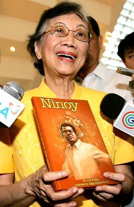 Si Tita Cory habang pinagmamalaki ang aklat ng kanyang apong si Jiggy Cruz ukol kay Ninoy Aquino sa isa sa kanyang mga huling public appearance sa DLSU Manila, 2009.