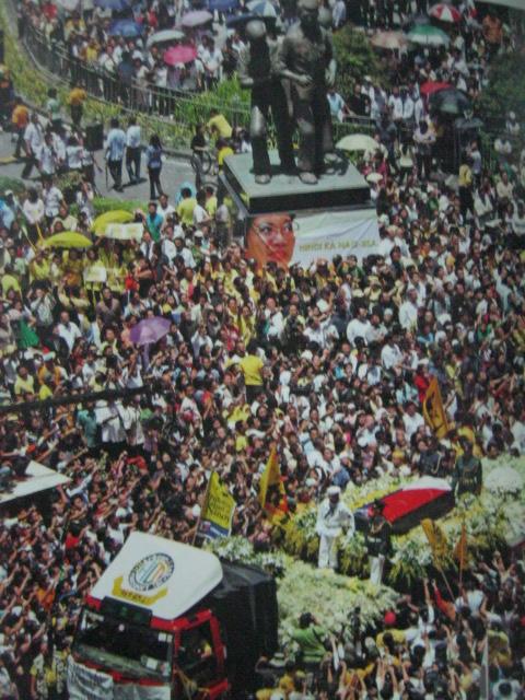 Nang magkasama ang monumento ni Ninoy at ng kabaong ng kanyang kabiyak.  Pareho na silang iniluklok ng bayan na mga bayani.  Mula sa Cory Magic:  Her People's Stories.