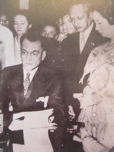 Si Quezon habang nilalagdaan ang pagboto ng mga kababaihan.  Mula sa Manuel Luis Quezon nina Edgardo J. Angara at Sonia P. Ner.