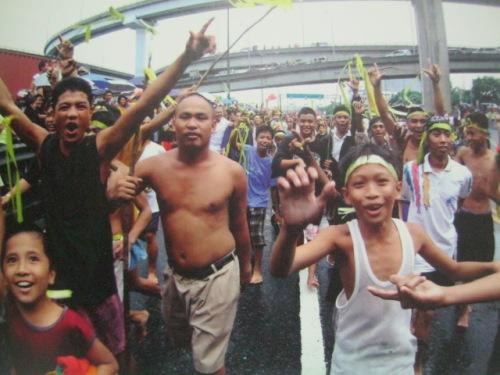 Ang mga tao ay nagbabatian ng Laban Sign.  Mula sa Cory Magic:  Her People's Stories.