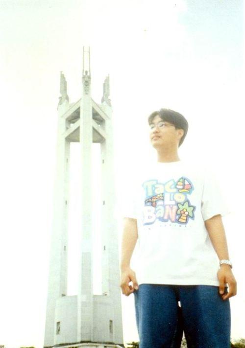 Si Xiao Chua sa harapan ng Quezon Memorial Monument na may 66 metrong taas na kumakatawan sa 66 na taon sa buhay ni Quezon.  Ang tatlong anghel ay kumakatawan sa pagluluksa at pagpupugay ng Luzon, Visayas at Mindanao.  Kuha ni Florenda Pangilinan mula sa Koleksyon ng Sinupan ng Aklatang Xiao Chua.