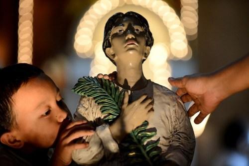 Isang bata ang nagbibigay respeto sa batang santo mula sa Visayas, si San Pedro Calúngsod.  Mula sa Rappler.